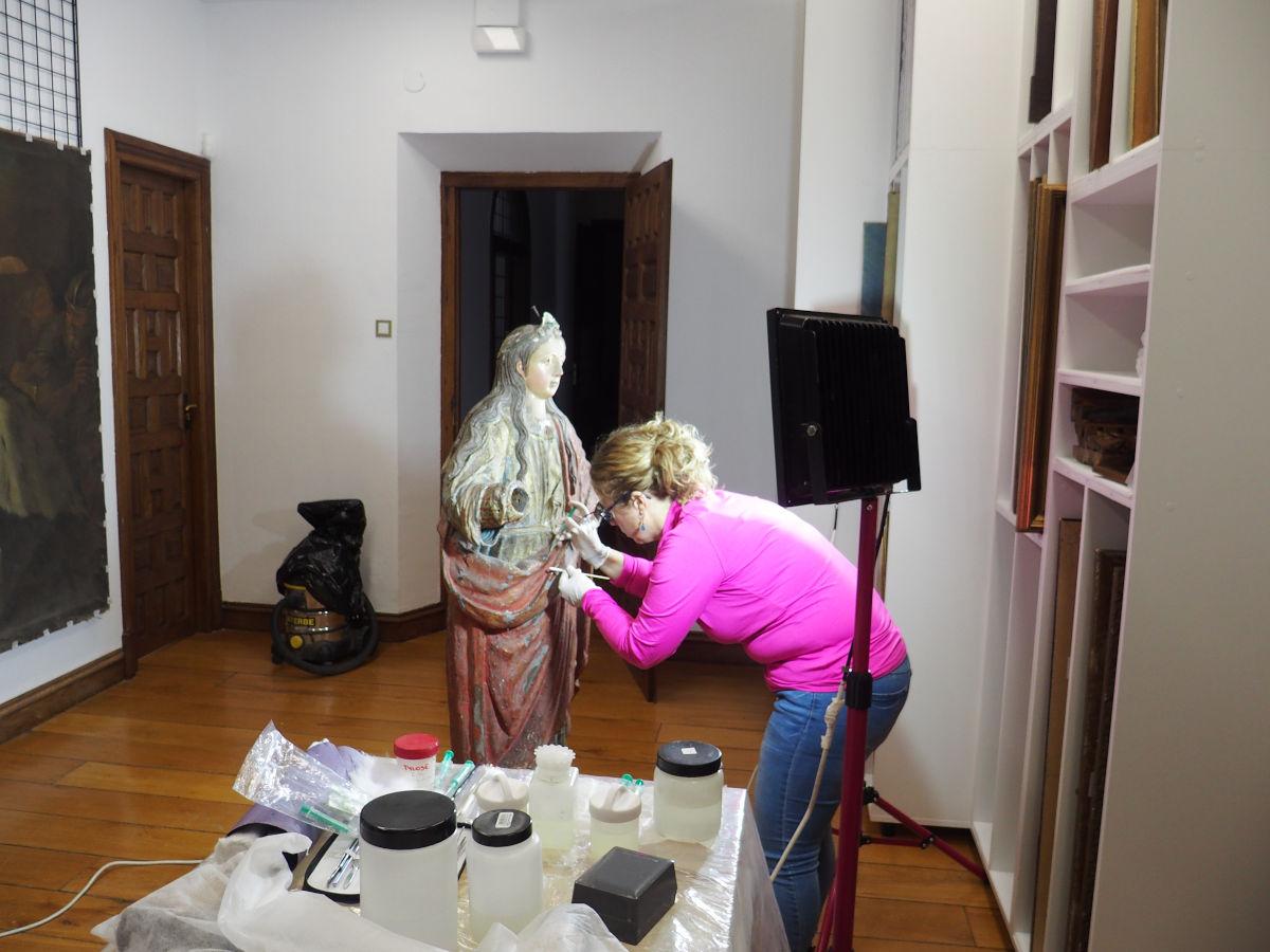 Restauradora aplicando labores de conservación en la escultura de Santa Barbararen